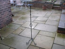 A tall metal stand with small bowl at its top.
