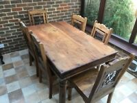 Solid Indian wood dining table and 6 chairs with metal design in the backs. Good condition