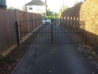 Black double iron gates with painted gold tops and black posts with adjustable hinges