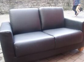 Black two seater faux leather type sofa.
