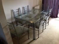 Metal and glass dining table and six matching chairs