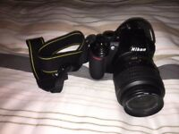Nikon D3100 DSLR with 18-55mm kit lens, charger, and carrier bag in near mint condition