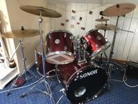 Sonor drum kit with base drum, two toms, floor Tom, high hat, snare, several symbols, cowbell