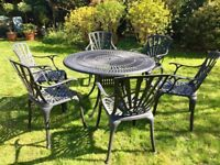 Circular, metal garden table and 6 matching chairs in dark grey