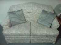 Two Seater Sofa in pink, grey and green.