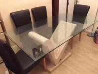 Glass dining table on stone feature stand