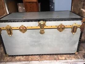 Large grey and black overpond foundation plywood and tin trunk.