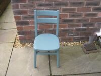 A four legged wooden child's chair painted in a blue/ grey finish.