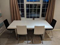 White dining table with 4 black and white chairs