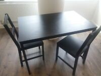 6 months black wooden dining table with chairs.