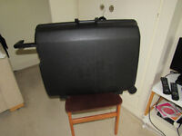Samsonite hard case with wheels at one end and sturdy pull handle