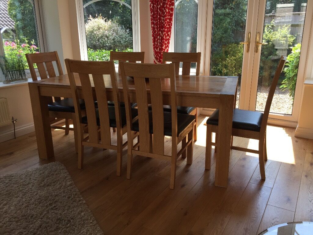 Solid oak dining table and six chairs with leather seats
