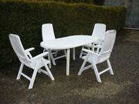 White garden furniture. An oval table and four reclining chairs. In good condition.
