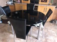 Black glass round kitchen table, 120cm extended. 4 matching chairs