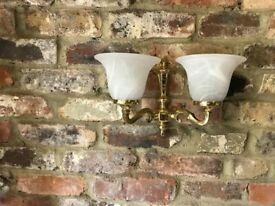 Set of three solid brass wall lights with glass shades