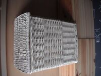 This is a small white wicker basket with attached lid