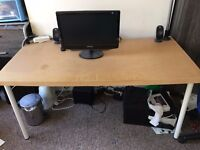 large ikea table, office chair, computer screen, book shelf and chest of 4 drawers