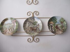 An unusual set of decorative plates complete with four wrought iron wall racks