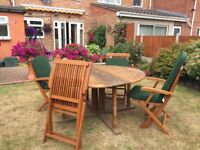 Garden folding patio set. Solid wood table and four chairs with cousions