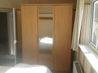 Light coloured wardrobe. Mirrored centre door
