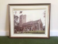 A framed print , or enlarged photo , of a north Devon church