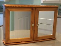 Pine bathroom cabinet with 2 shelves. Mirrored doors, in good condition