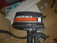 Small fishing/rowing boat with outboard motor and trailer.