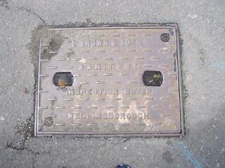 E brown cast iron manhole cover