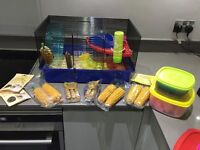 Two level hamster cage with accessories treats bedding and seeds in boxes
