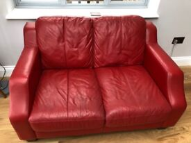 Red leather two-seater sofa in good condition