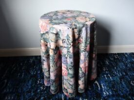 Small Circular MDF Table Covered by Blue Flowered Cloth