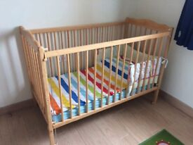 Light Wood Baby Cot with 2 levels and sliding down side.