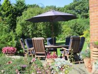Hardwood garden furniture set, table with lazy susan, 7 chairs with cushions and parasol.