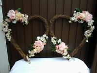 Wedding decorations. Matching pair of grapevine hearts decorated with silk flowers and leaves