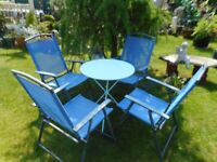 four blue folding garden chairs a blue folding table