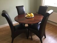 Dining table with four brown chairs