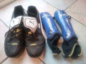 Black and white Puma football boots in size 8. Comes with junior size shin pads.
