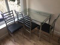 Glass table with 4 metal and leather chairs
