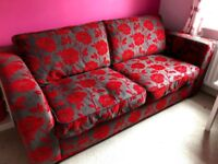 Charcoal two seat sofa with red flower pattern - good condition