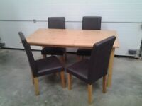 New Bargain. Wood Dining table and 4 Choc brown faux chairs. Boxed. Can deliver.