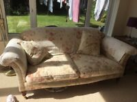 Laura Ashley sofa with chintz covers and cushions. Wooden feet with brass castors.