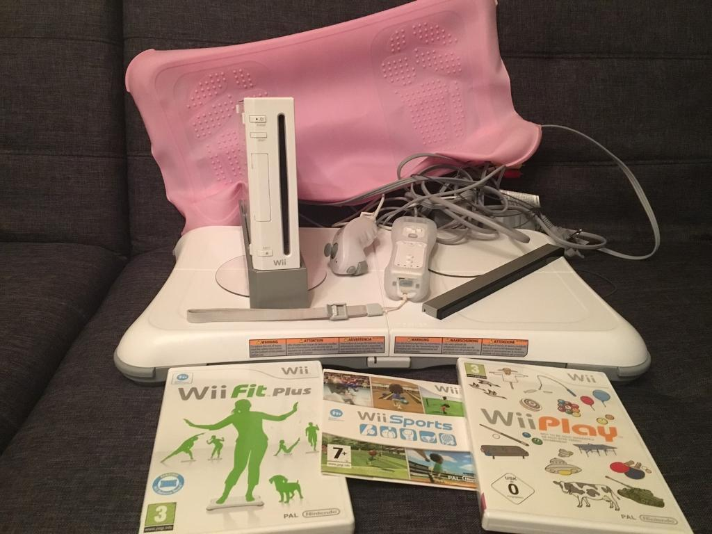 Wii console with remote and nunchuck and wii fit board with wii fit plus
