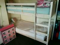 White wood single bunk bed frame with trundle and foam mattress