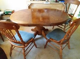 Solid extendable round table with four ornate chairs. In good condition for age .