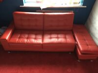 Modern red leather padded sofa bed with matching ottoman