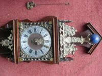 Ornate vintage Dutch 'atlas' wall clock with brass weights for winding.