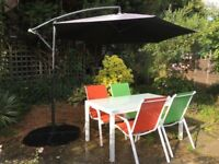 Garden furniture set all together -parasol, stylish glass table, coloured chairs and weights