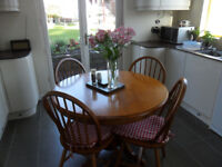 Kitchen table and four chairs with cushions.