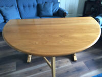 Ercol polished wooden oval dinning drop leaf table, seats 6-7.