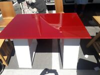 Table: Red glass, habitat table top and white trestle legs. Aprox 120cm by 70cm